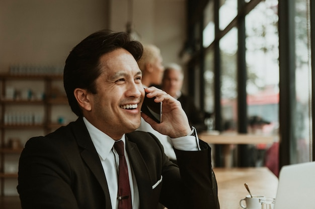 Glücklicher geschäftsmann am telefon in einem café