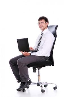 Glücklicher geschäftsmann auf stuhl mit laptop