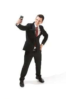 Glücklicher geschäftsmann, der am telefon über weißem hintergrund im studio-schießen spricht. lächelnder junger mann im anzug stehend und selfi-foto machend. business, karriere, erfolgskonzept.