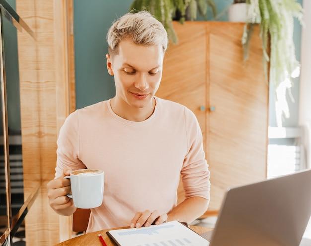 Glücklicher geschäftsmann, der an der cafeteria mit laptop und smartphone sitzt. geschäftsmann, der auf smartphone schreibt, während er in einem café sitzt, arbeitet und e-mail auf computer überprüft
