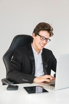 Glücklicher geschäftsmann, der an laptop im büro arbeitet