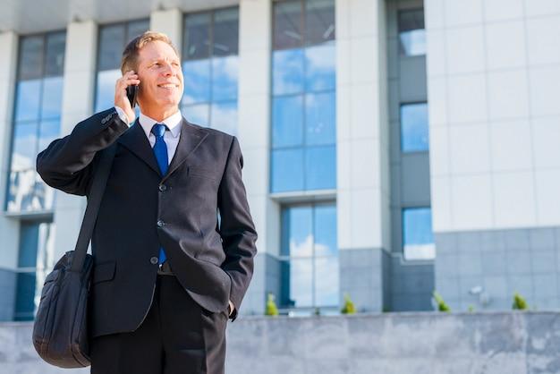 Glücklicher geschäftsmann, der auf smartphone vor gebäude spricht
