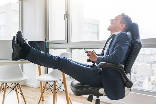 Glücklicher geschäftsmann, der auf stuhl am arbeitsplatz unter verwendung des handys sitzt