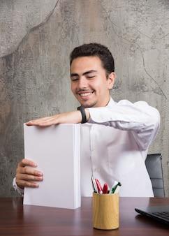 Glücklicher geschäftsmann, der bündel von papieren am schreibtisch hält.