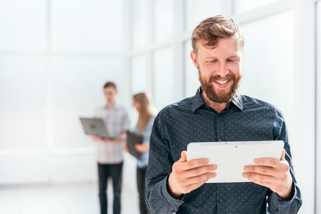 Glücklicher geschäftsmann, der den bildschirm seines digitalen tabletts betrachtet