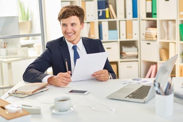 Glücklicher geschäftsmann, der dokumente liest
