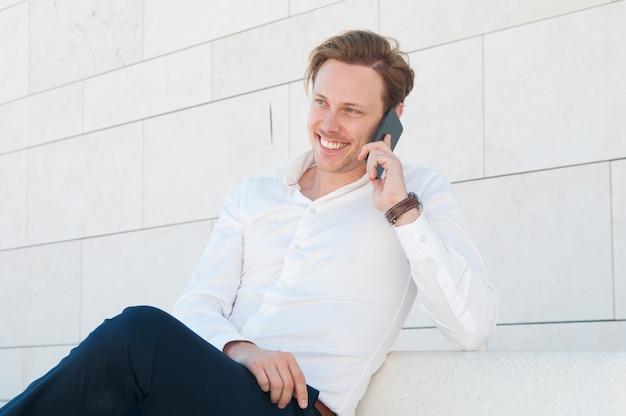 Glücklicher geschäftsmann, der draußen um smartphone auf bank ersucht