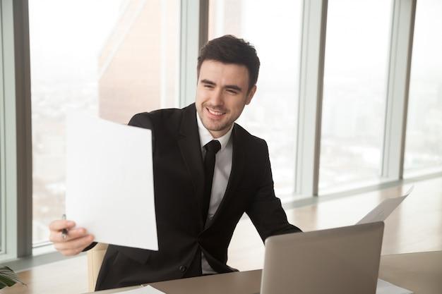 Glücklicher geschäftsmann, der finanzstatistikbericht, zufrieden gestellt hält