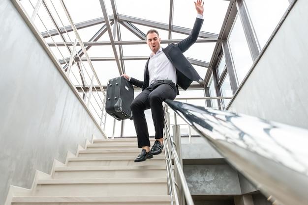 Glücklicher geschäftsmann, der formellen anzug trägt, der auf treppengeländer im modernen geschäftsgebäude gleitet. eile und freiheit konzept