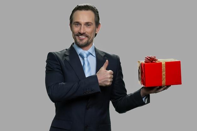 Glücklicher geschäftsmann, der geschenkbox hält und daumen oben zeigt. attraktiver kaukasischer mann, der geschenkbox auf grauem hintergrund zeigt.