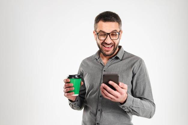 Glücklicher geschäftsmann, der handy trinkt kaffee. zur seite schauen.