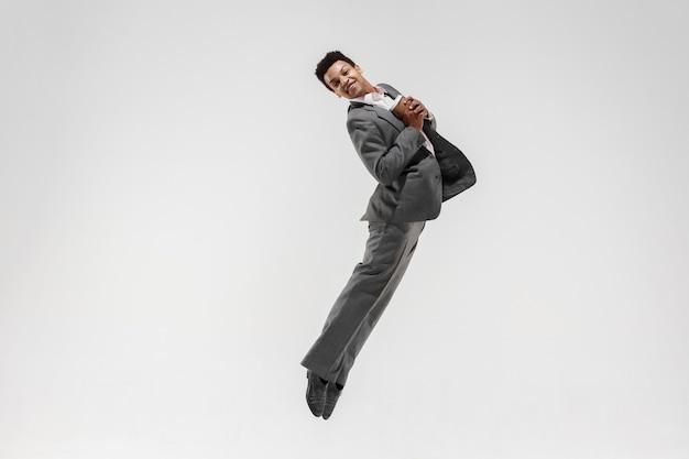 Glücklicher geschäftsmann, der in bewegung lokalisiert auf weißem studiohintergrund tanzt. flexibilität und anmut im geschäft. konzept der menschlichen emotionen. büro, erfolg, beruf, glück, ausdruckskonzepte