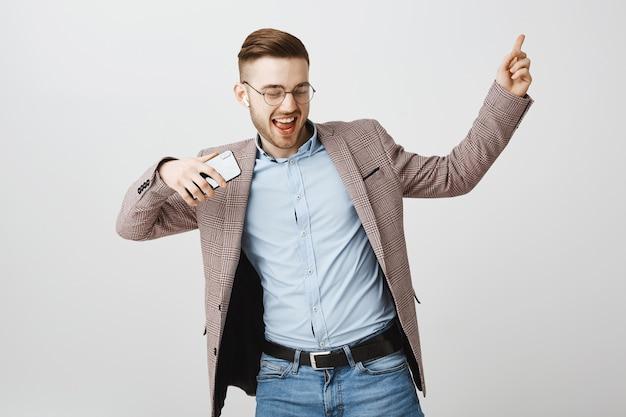 Glücklicher geschäftsmann, der in freude mit smartphone tanzt und musik in drahtlosen kopfhörern hört
