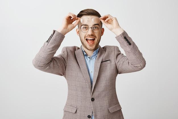 Glücklicher geschäftsmann, der neue brille am optikergeschäft anprobiert