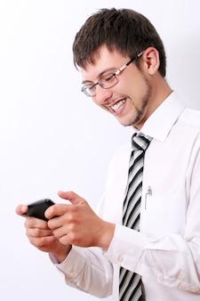 Glücklicher geschäftsmann, der sms auf seinem handy tippt