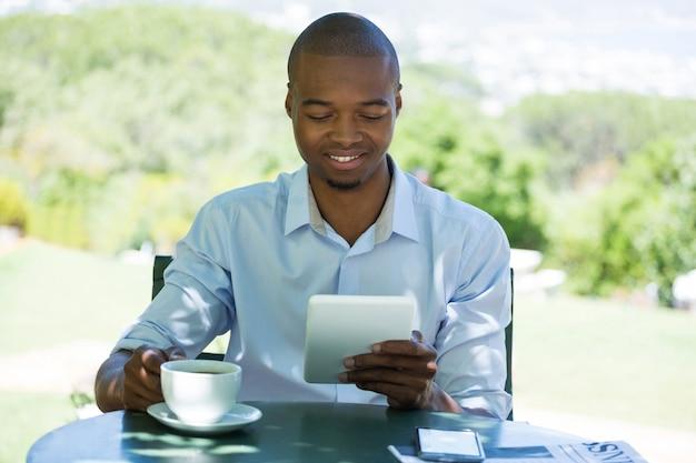 Glücklicher geschäftsmann, der tablet-computer beim kaffee im restaurant verwendet