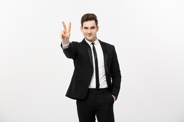 Glücklicher geschäftsmann, der zwei finger oder siegesgeste vor grauem hintergrund zeigt. erfolg im geschäfts-, job- und bildungskonzept. leerer copyspace-bereich für werbung, slogan oder text