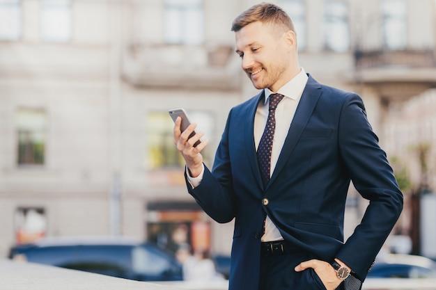 Glücklicher geschäftsmann hält hand in der tasche, die gesellschaftsanzug und armbanduhr trägt und intelligentes telefon verwendet