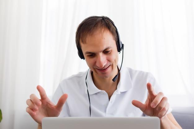 Glücklicher geschäftsmann im büro am telefon, kopfhörer, skype. schauende kamera
