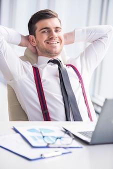 Glücklicher geschäftsmann ist in seinem büro entspannend.
