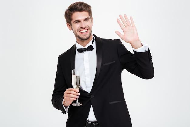 Glücklicher geschäftsmann mit champagner. winken