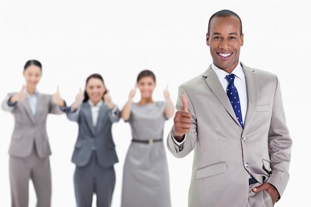 Glücklicher geschäftsmann mit einer hand in seiner tasche, die mit mitarbeitern zustimmt