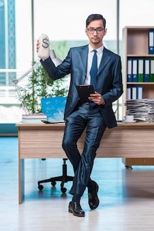 Glücklicher geschäftsmann mit geldsäcken im büro
