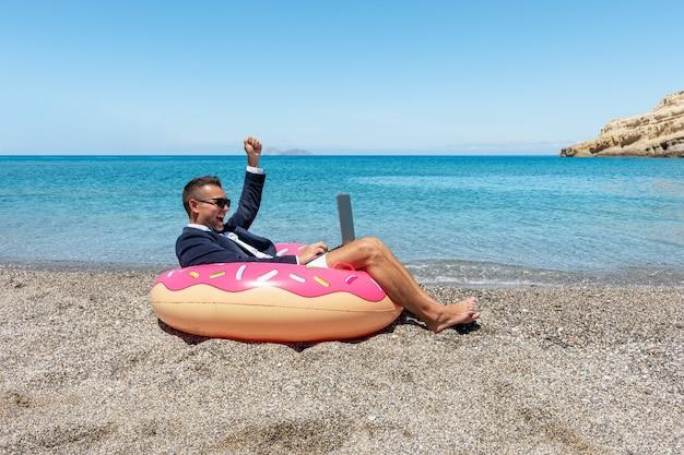 Glücklicher geschäftsmann mit laptop auf aufblasbarem donut am tropischen strand