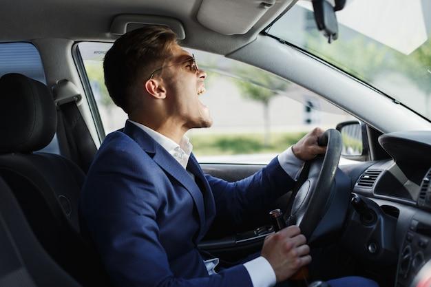 Glücklicher geschäftsmann sitzt shows seine gefühle, die am lenkrad innerhalb des autos sitzen
