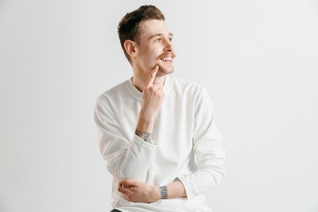 Glücklicher geschäftsmann stehend, lächelnd lokalisiert auf grauem studio