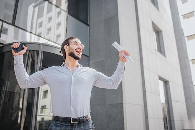 Glücklicher geschäftsmann steht beim bauen und hat freude und glück. er schreit laut und hält die hände beiseite und den körper hoch. es gibt telefon und ein stück papier.