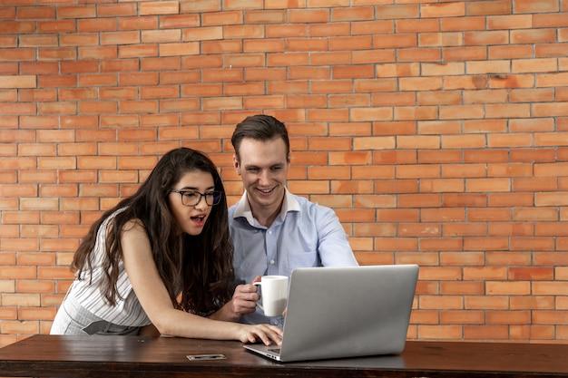 Glücklicher geschäftsmann und frau, die zusammen am laptop im café arbeiten