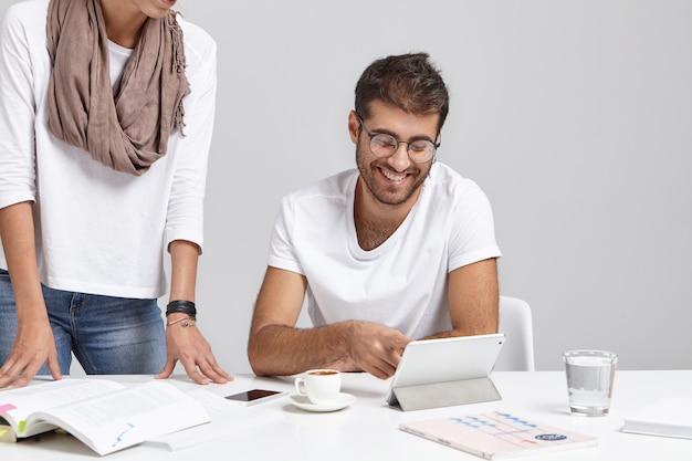 Glücklicher geschäftsmann und seine assistentin im büro nahe tisch, arbeiten mit dokumenten, trinken kaffee, benutzen elektronische geräte