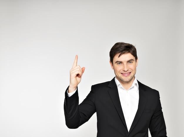 Glücklicher geschäftsmann zeigt mit dem finger im schwarzen anzug