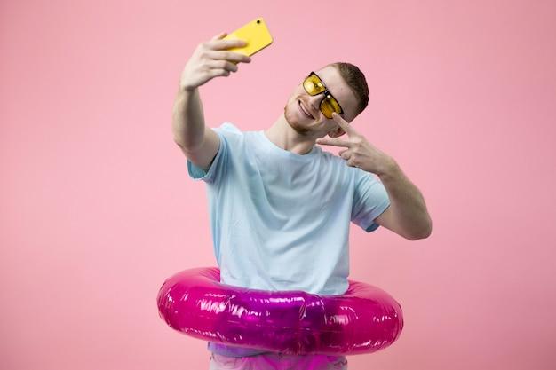 Glücklicher gestikulierender junger geschäftsmann im aufblasbaren schwimmring, der selfies macht