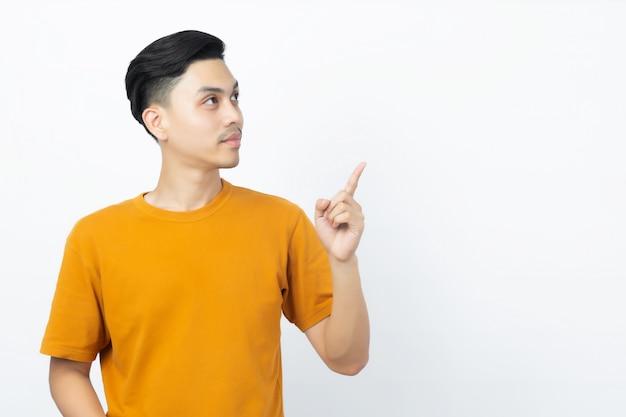 Glücklicher gesunder junger asiatischer mann, der mit seinem finger zeigt bis zum copyspace auf weiß lächelt.