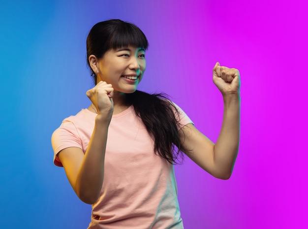 Glücklicher gewinner. asiatisches porträt der jungen frau auf gradientenstudiohintergrund in neon isoliert. schönes weibliches modell im lässigen stil. konzept der menschlichen emotionen, gesichtsausdruck, jugend, verkauf, anzeige. flyer