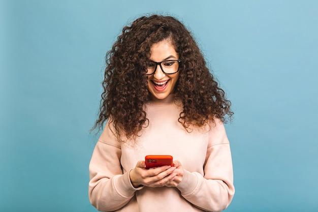 Glücklicher gewinner! porträt der überraschten überraschten lächelnden lässigen lockigen studentin, die smartphone lokalisiert über blauem hintergrund hält.