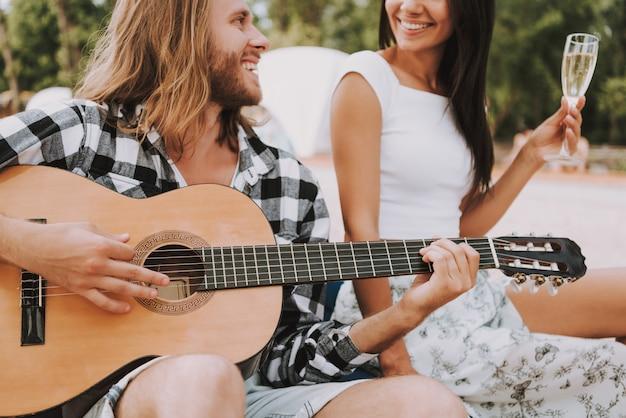 Glücklicher gitarrist und freunde am sommerstrand.