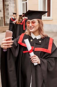 Glücklicher graduierter student, der selfie nimmt
