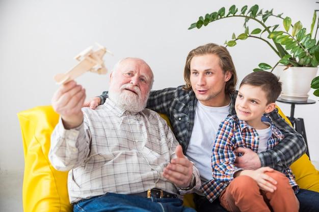 Glücklicher großvater, der mit hölzernem flugzeug spielt