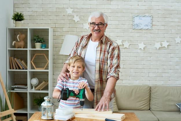 Glücklicher großvater, der mit kleinem enkel aufwirft