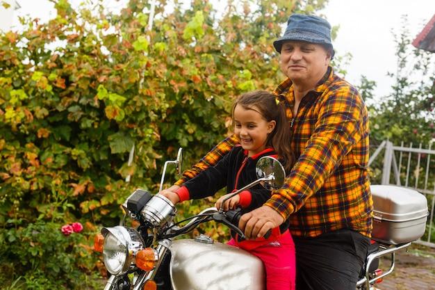 Glücklicher großvater und seine enkelin in lächelndem motorrad des handgemachten beiwagenfahrrades