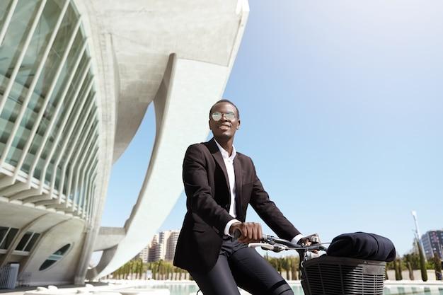 Glücklicher gut aussehender afrikanischer unternehmer, der fahrrad in städtischer umgebung auf seinem weg zum büro fährt. erfolgreicher dunkelhäutiger mitarbeiter, der die stadtfahrt mit dem schwarzen fahrrad genießt und am sommertag zur arbeit pendelt