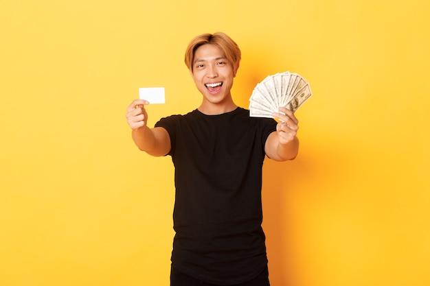 Glücklicher gut aussehender asiatischer kerl in der schwarzen freizeitkleidung, geld und kreditkarte zeigend, frech lächelnd, gelbe wand zeigend