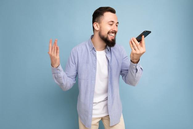 Glücklicher, gut aussehender junger bärtiger mann mit lässigem blauem hemd und weißem t-shirt