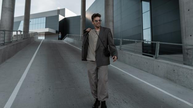 Glücklicher gutaussehender hipster-mann mit sonnenbrille im modischen grauen anzug mit handtasche, der die straße entlang in der stadt geht