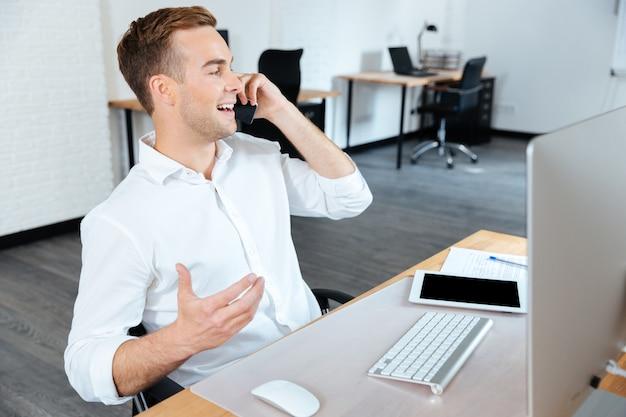 Glücklicher gutaussehender junger geschäftsmann, der im büro am handy arbeitet und spricht