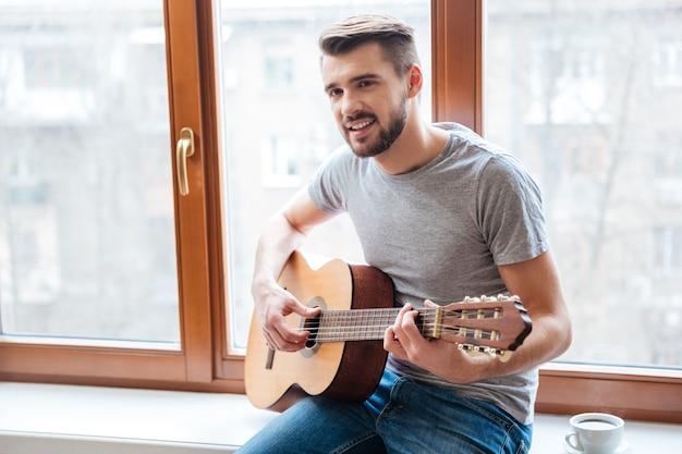 Glücklicher gutaussehender junger mann, der auf der fensterbank sitzt und zu hause gitarre spielt playing