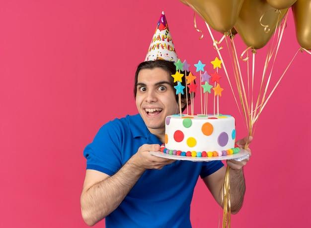 Glücklicher gutaussehender kaukasischer mann mit geburtstagsmütze hält heliumballons und geburtstagskuchen